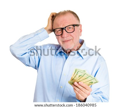 Closeup portrait, nerd senior mature man, black glasses, holding money in one hand, scratching head, not sure how to spend extra cash dollar bills, isolated white background. Human emotion, expression - stock photo
