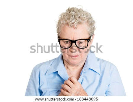 Closeup portrait, nerd, senior mature woman with black glasses,  playing with hands nervously, looking down, isolated white background. Mental health, emotion facial expression feeling - stock photo