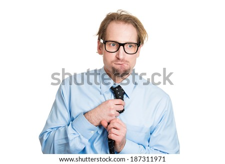 Closeup portrait, nerdy young guy with black glasses fidgeting with tie, looking funny, scared, craving something, anxious, isolated white background. Human facial expressions, emotions, feelings - stock photo