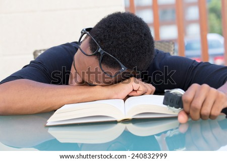 Closeup portrait, nerdy young man in big black glasses holding watch, falling very tired of reading, fast asleep, isolated outdoors outside background. Cramming for all-nighter - stock photo
