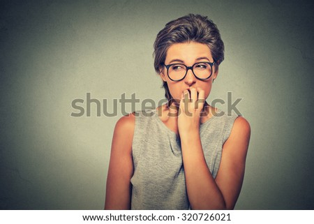 Closeup portrait nervous looking woman biting her fingernails craving something anxious isolated grey wall background with copy space. Negative human emotion facial expression body language perception - stock photo