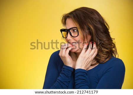 Closeup portrait nervous woman with glasses biting her fingernails craving something, anxious isolated yellow background copy space. Negative human emotion facial expression body language perception - stock photo