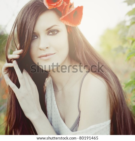 Closeup portrait of a attractive girl with poppies in her hair - stock photo