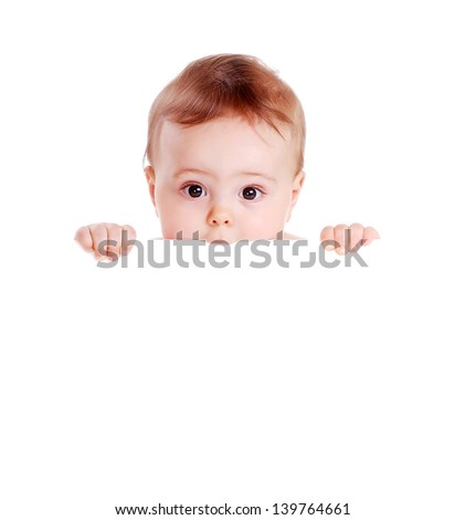 Closeup portrait of a baby boy biting the blank board