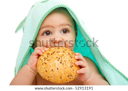 Closeup portrait of a baby eating seeded bun - stock photo