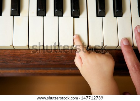 Closeup portrait of a baby hand playing piano with adult hand - stock photo