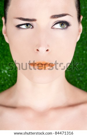 Closeup portrait of a beautiful angry woman with glossy lips looking away on green background - stock photo