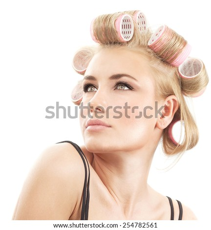 Closeup portrait of a beautiful blonde female with curlers on hair isolated on white background, making fashionable hairstyle, beauty salon makeover concept - stock photo