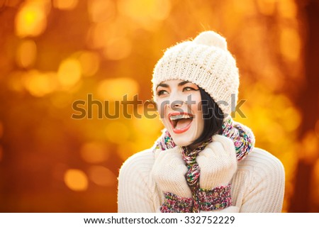 Closeup portrait of a beautiful brunette in the autumn park - stock photo