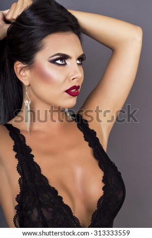 Closeup portrait of a beautiful brunette lady posing in sexy black lingerie over gray background - stock photo