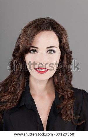 Closeup portrait of a beautiful brunette woman smiling isolated on gray background - stock photo