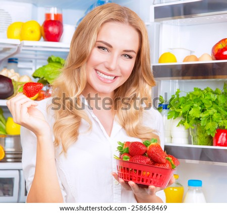 Closeup portrait of a beautiful female eating strawberry, standing next to open fridge full of fruits and vegetables, dieting and healthy eating concept, enjoying healthy living and wellness - stock photo