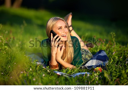 closeup portrait of a beautiful girl in a field talking on the phone