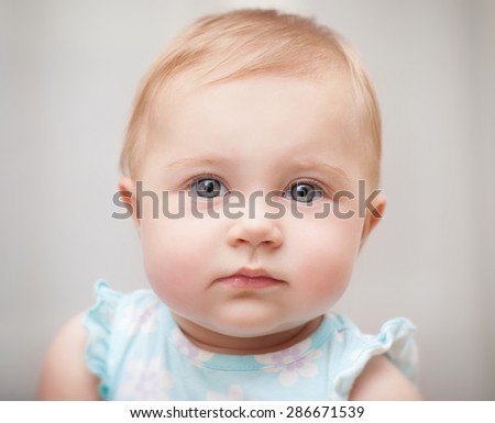 Closeup portrait of a beautiful little baby girl isolated on gray background, carefree childhood, precious innocent kid
