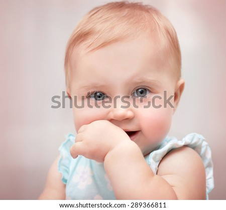 Closeup portrait of a beautiful little baby girl with hand in the mouth over pastel pink background, carefree childhood, precious innocent kid - stock photo