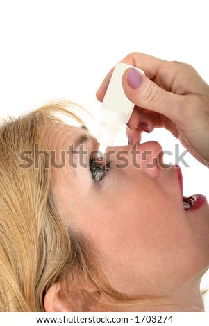 Closeup portrait of a beautiful middle-aged woman using eyedrops.  Shot isolated on white background.