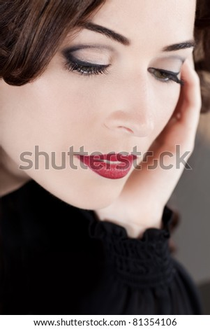 Closeup portrait of a beautiful middle aged woman with red lips looking down - stock photo