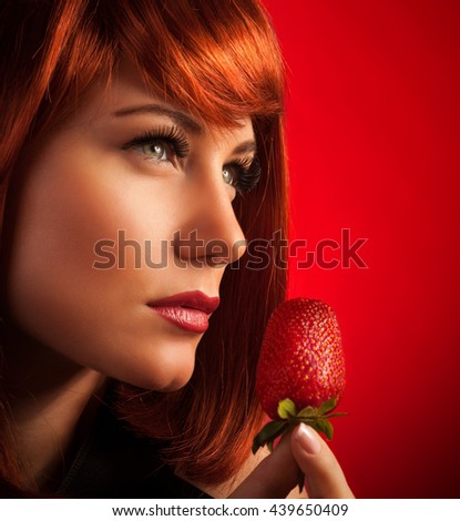 Closeup portrait of a beautiful seductive female with fresh juicy strawberry, red background, enjoyment and temptation - stock photo