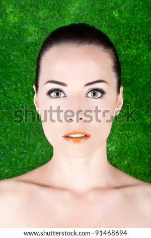 Closeup portrait of a beautiful serious woman with green eyes in studio against green