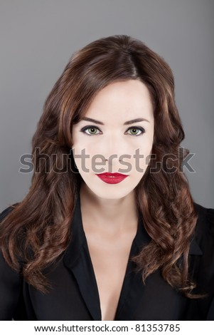 Closeup portrait of a beautiful sexy woman with brown hair and red lips isolated on gray background - stock photo