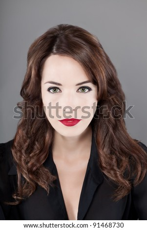 Closeup portrait of a beautiful sexy woman with brown hair and red lips isolated on gray background