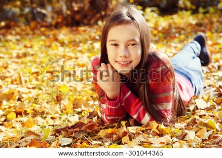 closeup portrait of a beautiful smiling teenage girl with yellow leaves in autumn