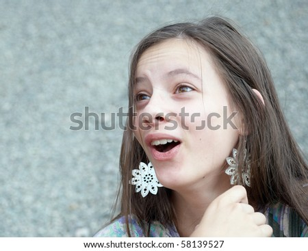 Closeup portrait of a beautiful surprised girl with big earrings - stock photo
