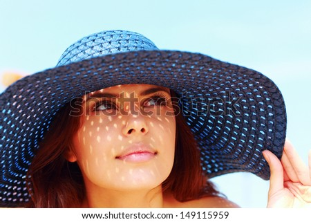 Closeup portrait of a beautiful woman in hat looking up