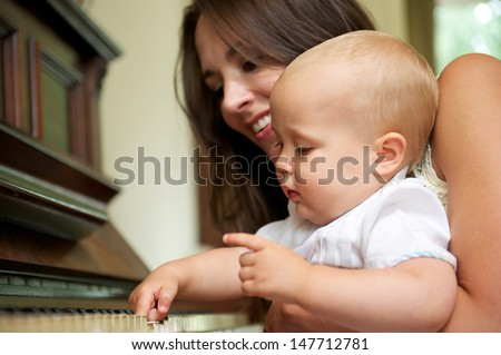 Closeup portrait of a beautiful woman teaching baby to play piano - stock photo