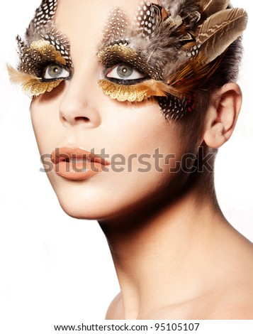 Closeup portrait of a beautiful woman wearing striking creative eye makeup with birds feathers. - stock photo