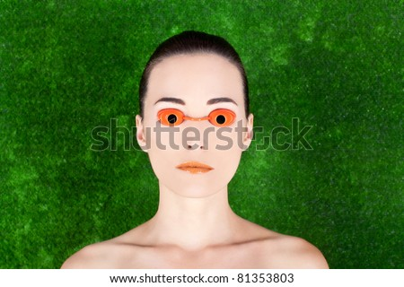 Closeup portrait of a beautiful woman wearing tanning bed glasses on green background - stock photo