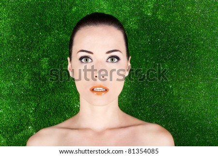 Closeup portrait of a beautiful woman with green eyes in studio against green - stock photo
