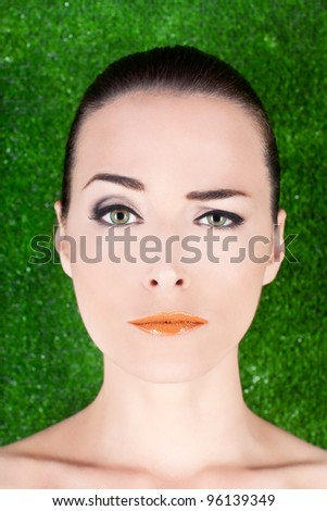 Closeup portrait of a beautiful woman with green eyes raising an eyebrow in studio against green - stock photo