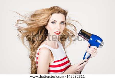 Closeup portrait of a beautiful woman with long chestnut red straight hair holding hairdryer. fashion studio portrait - stock photo