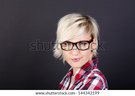 Closeup portrait of a beautiful young blond woman against black background - stock photo