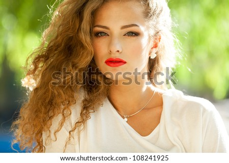 Closeup portrait of a beautiful young brunette woman with natural makeup, perfect skin and gorgeous curly hair outdoors - stock photo