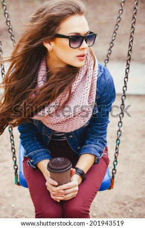 Closeup portrait of a beautiful young girl sitting on a swing, holding drink in her hands. Wearing sunglasses. Windy summer day. Outdoors - stock photo
