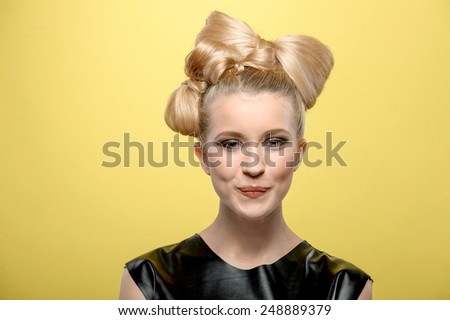 Closeup portrait of a beautiful young girl with blonde hair and orange lips. Smiling and looking to the camera. isolated on the yellow background - stock photo