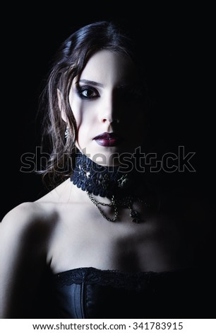 Closeup portrait of a beautiful young goth girl in cold tones  - stock photo