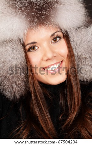 Closeup portrait of a beautiful young lady in fur hat isolated on dark background