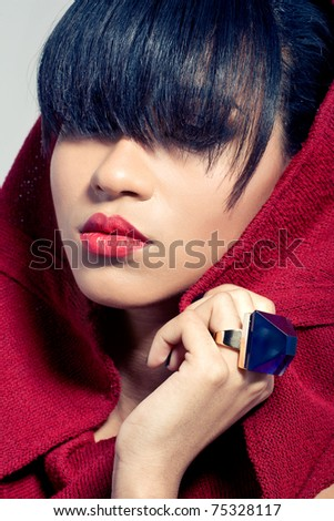 Closeup portrait of a beautiful young woman wearing fashionable red dress and jewelry - stock photo