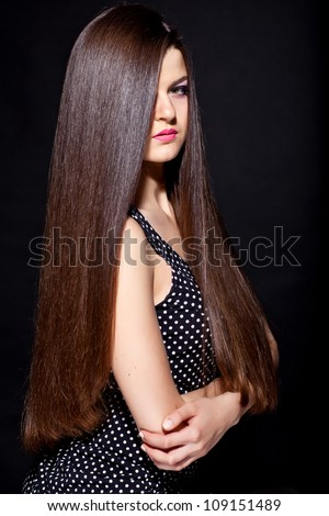 closeup portrait of a beautiful young woman with elegant long shiny hair from back , hairstyle , on a black background , healthy straight hair - stock photo