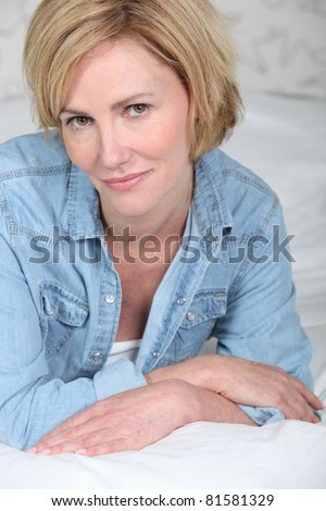 Closeup portrait of a blonde woman lying on a bed in a denim shirt - stock photo