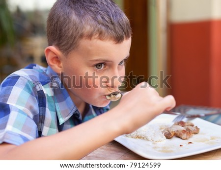 Closeup portrait of a boy eating in a restaurant - stock photo
