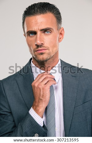 Closeup portrait of a businessman straightening his tie isolated on a white background - stock photo