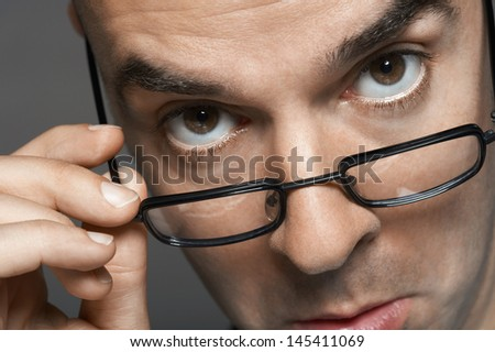 Closeup portrait of a businessman with hand on glasses making a face against gray background - stock photo