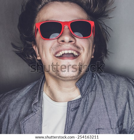 closeup portrait of a casual young man with sunglasses jumping - stock photo
