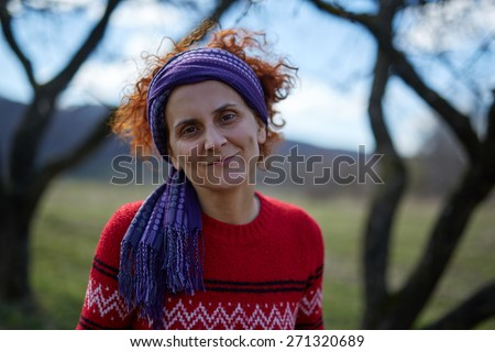 Closeup portrait of a caucasian peasant woman smiling outdoor - stock photo