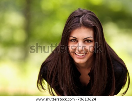 Closeup portrait of a cheerful happy latin young woman outdoor - stock photo