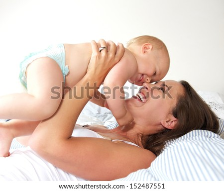 Closeup portrait of a cheerful mother and cute baby playing  - stock photo